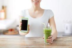 关闭有智能手机和绿色汁液的妇女 免版税库存照片