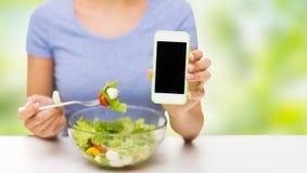 关闭有智能手机的妇女吃沙拉的  库存照片
