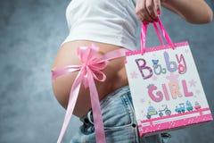 关闭有桃红色丝带的逗人喜爱的怀孕的腹部肚子 免版税库存照片