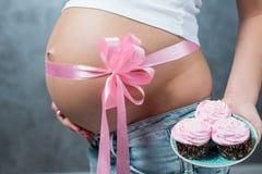 关闭有桃红色丝带的逗人喜爱的怀孕的腹部肚子 免版税库存图片