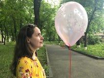 关闭有桃红色气球的一名年轻深色的妇女在她的手上 侧视图 免版税库存图片