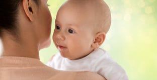 关闭有母亲的愉快的婴孩在绿色 库存照片