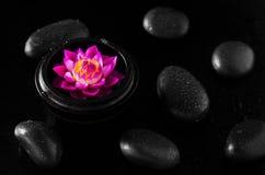 关闭有水lilly花形状的温泉肥皂在黑色后面 免版税库存图片
