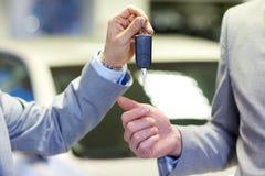 关闭有汽车钥匙的男性手在自动沙龙 免版税库存图片