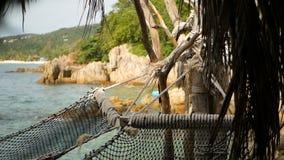 关闭有热带海洋的浪漫舒适空的吊床背景的 对天堂,旅行的假期向海 股票录像