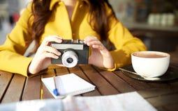 关闭有照相机的妇女在城市咖啡馆 免版税库存图片