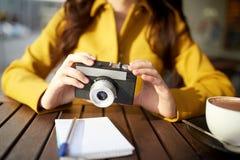 关闭有照相机的妇女在城市咖啡馆 库存图片