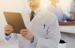 关闭有片剂个人计算机的愉快的医生在诊所 库存图片