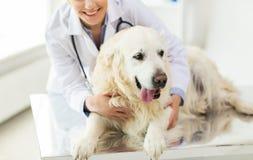 关闭有猎犬狗的狩医在诊所 免版税库存照片