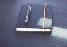 关闭有现代机械铅笔的黑笔记本在黑w 免版税图库摄影
