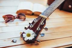 关闭有玻璃和书的古典吉他头 免版税图库摄影