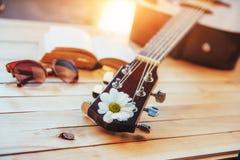 关闭有玻璃和书的古典吉他头 免版税库存图片