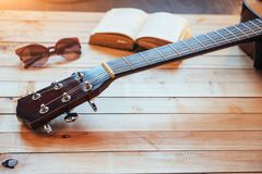 关闭有玻璃和书的古典吉他头 库存照片