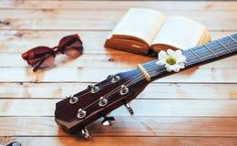 关闭有玻璃和书的古典吉他头 库存图片