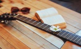 关闭有玻璃和书的古典吉他头 图库摄影