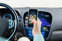 关闭有电话的人在汽车的智能手机 免版税图库摄影