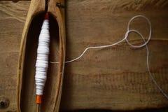 关闭有白色螺纹的短管轴在机织织物的木地方设备 库存图片