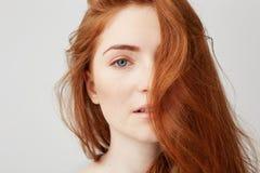 关闭有看在白色背景的红色头发的年轻嫩美丽的女孩照相机 库存照片