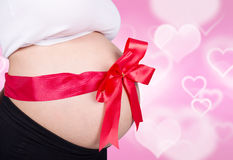 关闭有红色丝带礼物的孕妇在心脏b的腹部 库存图片