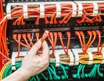 关闭有红色网络缆绳和缆绳的手被连接到开关 免版税库存图片