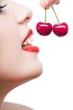 关闭有红色嘴唇的女孩吃两个莓果的  免版税库存照片