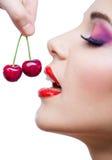 关闭有红色嘴唇的妇女吃两个莓果的观点的 免版税库存照片