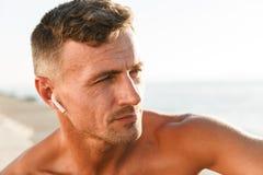关闭有耳机的英俊的赤裸上身的运动员 免版税图库摄影