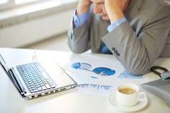 关闭有膝上型计算机的被注重的老人在办公室 免版税库存照片