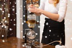 关闭有虹吸管咖啡壶和罐的妇女 免版税图库摄影