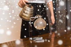 关闭有虹吸管咖啡壶和罐的妇女 图库摄影