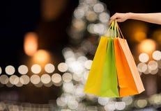 关闭有购物袋的手在圣诞节 免版税图库摄影