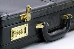 关闭有金黄号码锁的一个老皮革公文包 库存照片
