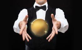 关闭有金黄硬币的魔术师在黑色 免版税库存图片
