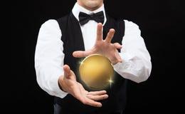 关闭有金黄硬币的魔术师在黑色 免版税库存照片