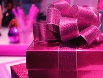 关闭有铺砂机生动的桃红色丝带弓的一个方形的发光的生动的桃红色礼物盒,选择聚焦 免版税库存图片