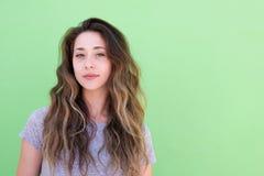 关闭有长的头发的少妇反对绿色背景 免版税图库摄影