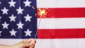 关闭有闪烁发光物的手在美国国旗 股票录像