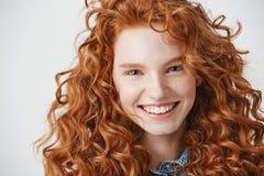 关闭有雀斑的微笑红头发人美丽的女孩看在白色背景的照相机 库存照片
