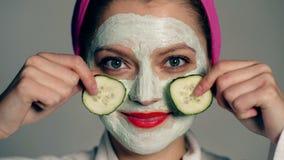 关闭有面罩的一个女孩和在闭上她的眼睛用在灰色背景的黄瓜的她的头的一块毛巾 股票录像