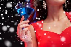 关闭有鸡尾酒的美丽的妇女在晚上 免版税库存图片