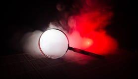 关闭有黑把柄的唯一放大镜,倾斜在橙红烟黑暗背景的木表 超现实的backg 图库摄影