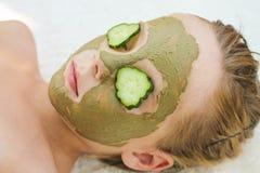 关闭有黄瓜和黏土面部面具的美丽的女孩  免版税库存图片