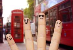 关闭有兴高采烈的面孔的四个手指 免版税库存图片