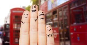 关闭有兴高采烈的面孔的四个手指 免版税库存照片