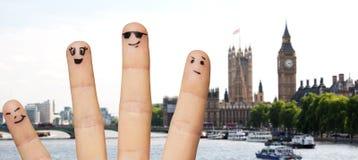 关闭有兴高采烈的面孔的手指在伦敦 免版税库存图片
