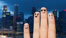 关闭有兴高采烈的面孔的手指在城市 库存图片