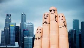 关闭有兴高采烈的面孔的手指在城市 免版税库存照片