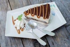关闭有banoffee蛋糕的匙子倒在白色盘的焦糖 免版税库存图片