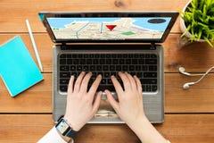 关闭有gps导航员地图的妇女在膝上型计算机 免版税库存图片