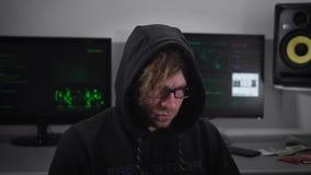关闭有smartwatch开会的一位间谍和有计算机显示器的使用膝上型计算机在他后 镜片的犯罪人 股票视频